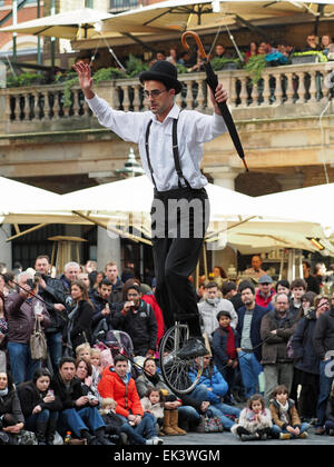 A tightrope walker on a unicycle entertaining a crowd in Covent Garden London UK - Stock Photo