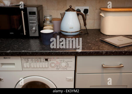 All appliances on kitchen worktop being used at once - Stock Photo