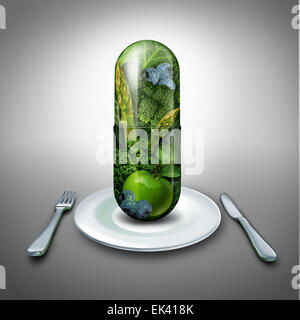 Food supplement concept as a giant pill or medicine capsule with fresh fruit and vegetables inside on a table place - Stock Photo