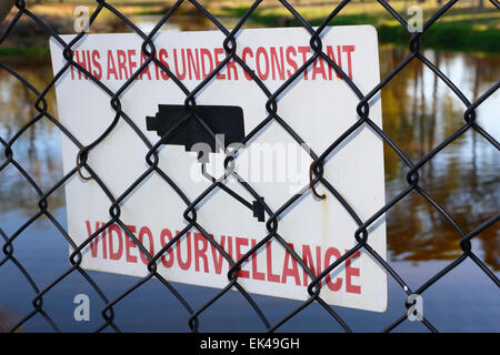 Warning sign indicating that this area is under constant video surveillance. Note the incorrect spelling of surveillance. - Stock Photo