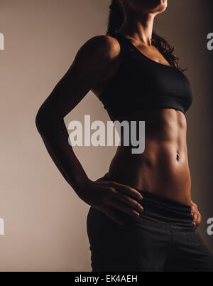 Cropped image of muscular young woman posing in sportswear. Fit female model with perfect torso in studio. - Stock Photo
