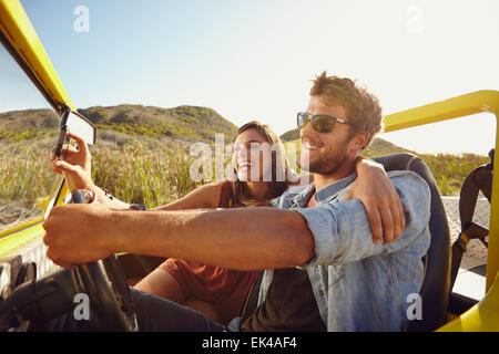Man driving beach buggy with woman taking selfie on her smart phone. Couple having fun on road trip on a summer - Stock Photo