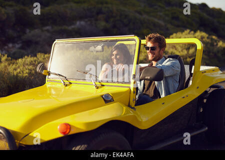Shot of a handsome young man driving a buggy car in the countryside with his girlfriend. Cheerful young couple on - Stock Photo