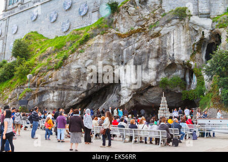 Massabielle grotto, statue of Our Lady of Lourdes and pilgrims. Lourdes city.  Midi-Pyrenees region, France, Europe. - Stock Photo