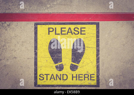 PLEASE STAND HERE foot sign or symbol on the floor, Retro filter effect - Stock Photo