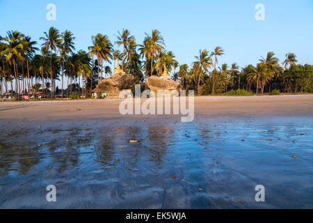 Two golden pagodas sitting on top of rocks found on the beach of Ngwe Saung, west coast of Myanmar - Stock Photo