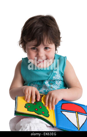 Happy three year old girl showing a drawing in her picture book on white background - Stock Photo