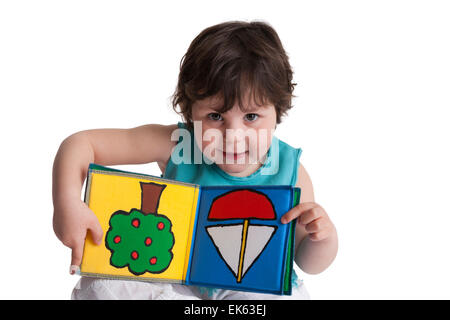 Happy three year old girl showing a drawing in her upside down book on white background - Stock Photo