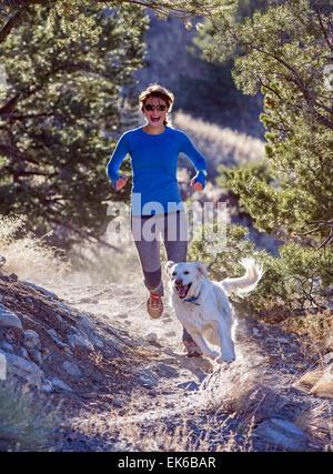 Happy beautiful young woman & dog running on mountain trails near Salida, Colorado, USA - Stock Photo