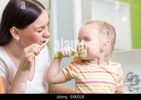 cute mom teaching kid teeth brushing - Stock Photo