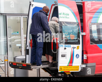 An elderly lady on a lift at the rear of a disabled park and ride hybrid minibus at a shopping centre in Coventry. - Stock Photo