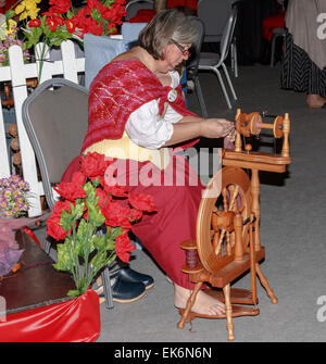 Lady in traditional costume using a spinning wheel - Stock Photo