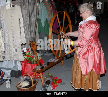 Woman (50-60 years) spinner in traditional costume using a hand driven spinning wheel to spin alpaca yarn - Stock Photo