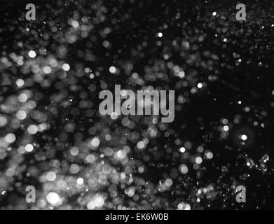 Bokeh lights on black background, defocused shot of flying drops of water in the air, levitating - Stock Photo