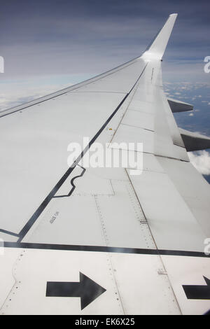 A right wing of Boeing 737-800 jet plane during flight on high altitude - Stock Photo
