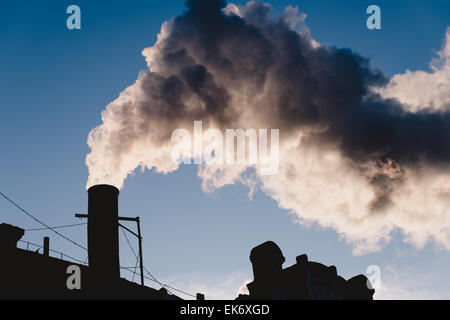 Electrical power industrial smoking chimney, steam against clear sky - Stock Photo
