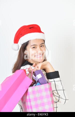 Shopping pretty young smiling woman in Santa Cap holding shopping bags. - Stock Photo
