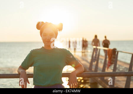 Portrait of confident young woman leaning on railing at pier over sea - Stock Photo