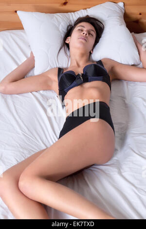 Beautiful young multi racial woman sleeping in bed - Stock Photo