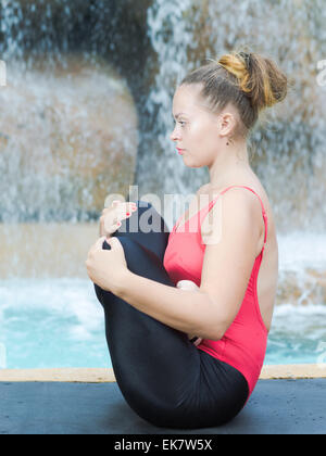 Woman practicing yoga near waterfall. Fetus Pose. Garbhasana - Stock Photo