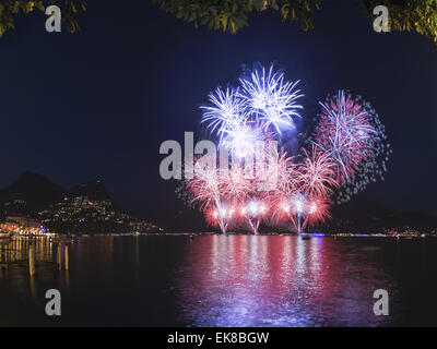 Fireworks on the Lugano lake in a summer evening, Switzerland - Stock Photo