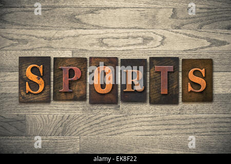 The word 'SPORTS' theme written in vintage, ink stained, wooden letterpress type on a wood grained background. - Stock Photo