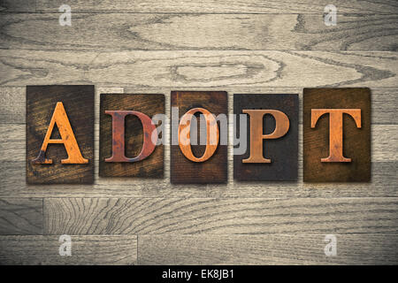 The word 'ADOPT' theme written in vintage, ink stained, wooden letterpress type on a wood grained background.' theme - Stock Photo