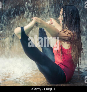 Woman practicing yoga near waterfall. Boat Pose. Navasana - Stock Photo