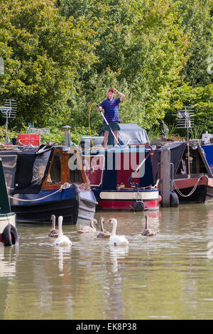Man cleaning narrowboat moored on the Kennet and Avon Canal, Devizes, Wiltshire, England, UK - Stock Photo