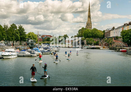 Stand Up Paddle Boarders taking a leisurely paddle around Bristol's Floating Harbour on a summer's day. - Stock Photo