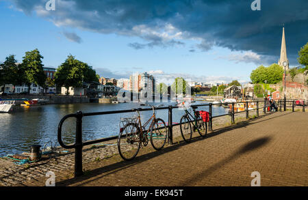 Bikes parked against railings on a stretch of path along side Bristol's Floating Harbour near St Mary Redcliffe. - Stock Photo