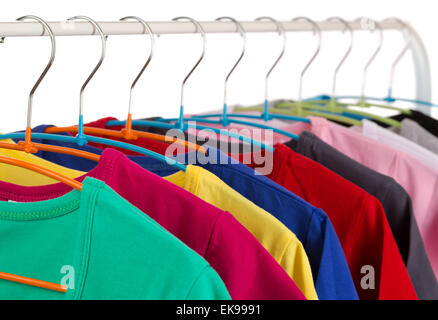 Colorful shirts on hangers, isolate on white. - Stock Photo