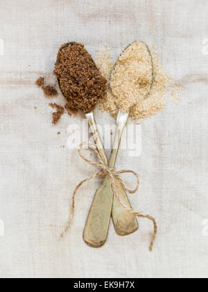 Muscovado and demerara brown sugars on two silver spoons placed on a rustic linen tablecloth. Vertical orientation. - Stock Photo