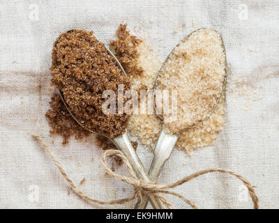 Horizontal photo muscovado and demerara organic brown sugars on two silver spoons placed on a rustic linen tablecloth, - Stock Photo