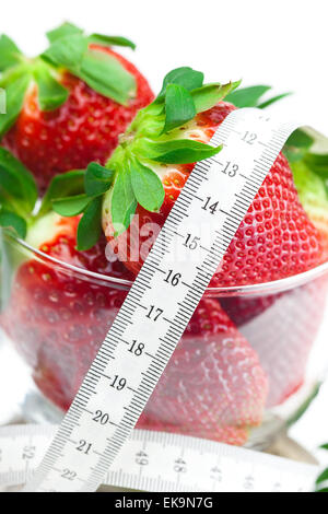 big juicy red ripe strawberries in a glass bowl and measure tape - Stock Photo
