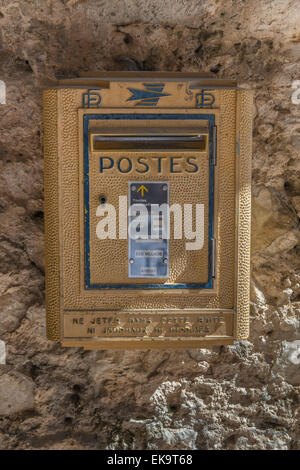 A faded yellow French postal service mailbox on a stone wall used for sending mail and post - Stock Photo