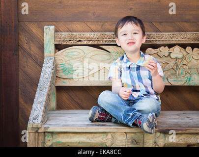 Cute Relaxed Mixed Race Boy Sitting on Bench Eating His Sandwich. - Stock Photo