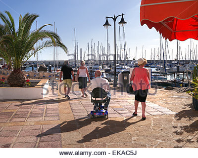 Group of tourists including man using a mobility scooter enjoying the sun at Marina Rubicon Lanzarote Canary Islands - Stock Photo