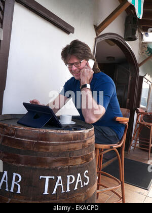 Man using his iPhone 6 and iPad Air tablet computer abroad at alfresco Spanish Tapas restaurant bar - Stock Photo