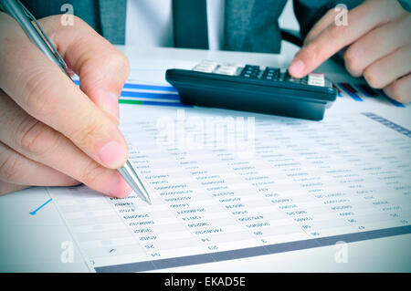 closeup of a young businessman checking accounts with a calculator in his office - Stock Photo