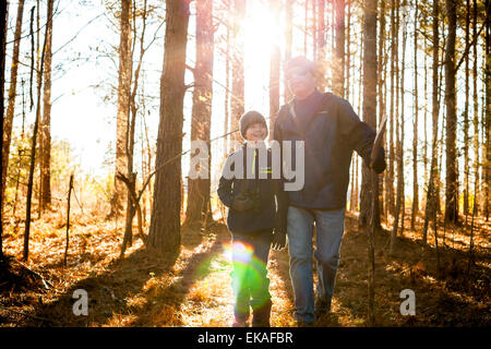 Father and son hiking in woods - Stock Photo
