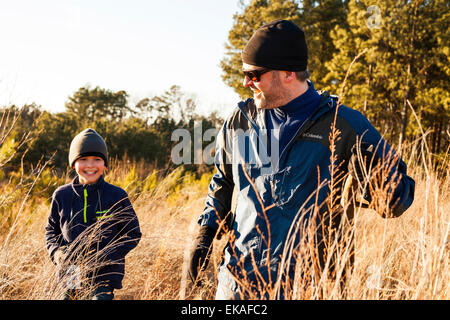 Father and son hiking in field - Stock Photo