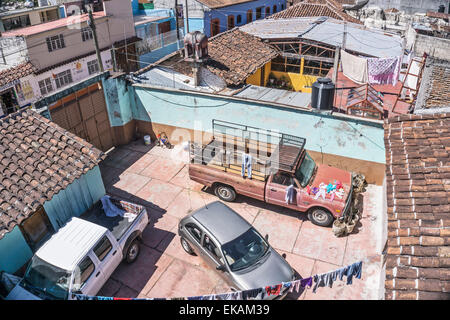 view down on courtyards hidden from street where old truck is seen used as drying surface for clothes overflowing - Stock Photo