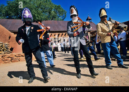 Wearing their veiled headresses and carrying ceremonial tridents, mysterious Matachine dancers and a young girl - Stock Photo