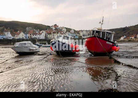 A group of 3 fishing boats on the sand at low tide in Staithes North Yorkshire. - Stock Photo