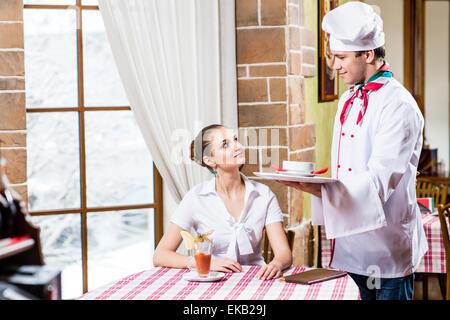 Chef brings a dish pretty woman in a restaurant - Stock Photo