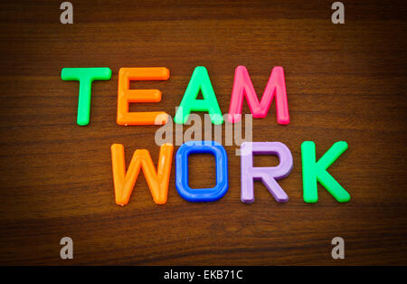 Team work in colorful toy letters on wood background - Stock Photo