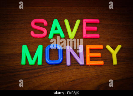 Save money in colorful toy letters on wood background - Stock Photo