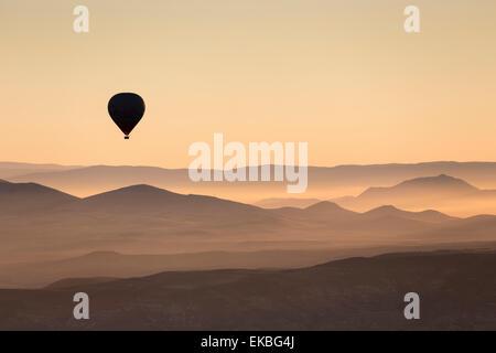 Single hot air balloon over a misty dawn sky, Cappadocia, Anatolia, Turkey, Asia Minor, Eurasia - Stock Photo