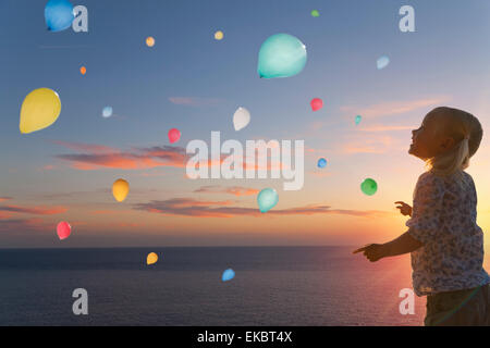 Girl watching balloons floating in evening sky - Stock Photo